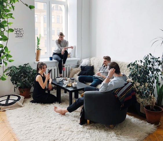 group of people lounging in the living room of an apartment